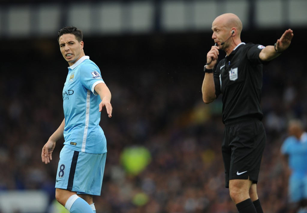 Manchester City's Samir Nasri (L) argues with referee Anthony Taylor (R) earning himself a yellow card during the English Premier League soccer match between Everton and Manchester City at Goodison Park, Liverpool, Britain, 23 August 2015. EPA/PETER POWELL