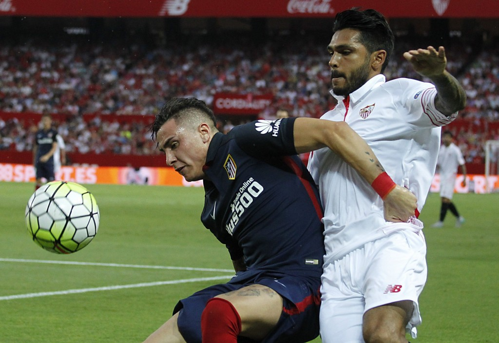 Sevilla's Benoit Tremoulinas (R) vies for the ball with Jose Gimenez (L) from Atletico Madrid during the Spanish Primera Division match between Sevilla and Atletico Madrid at the Sanchez Pijuan stadium in Seville, Spain, 30 August 2015. (Photo by PACO PUENTES/EPA)