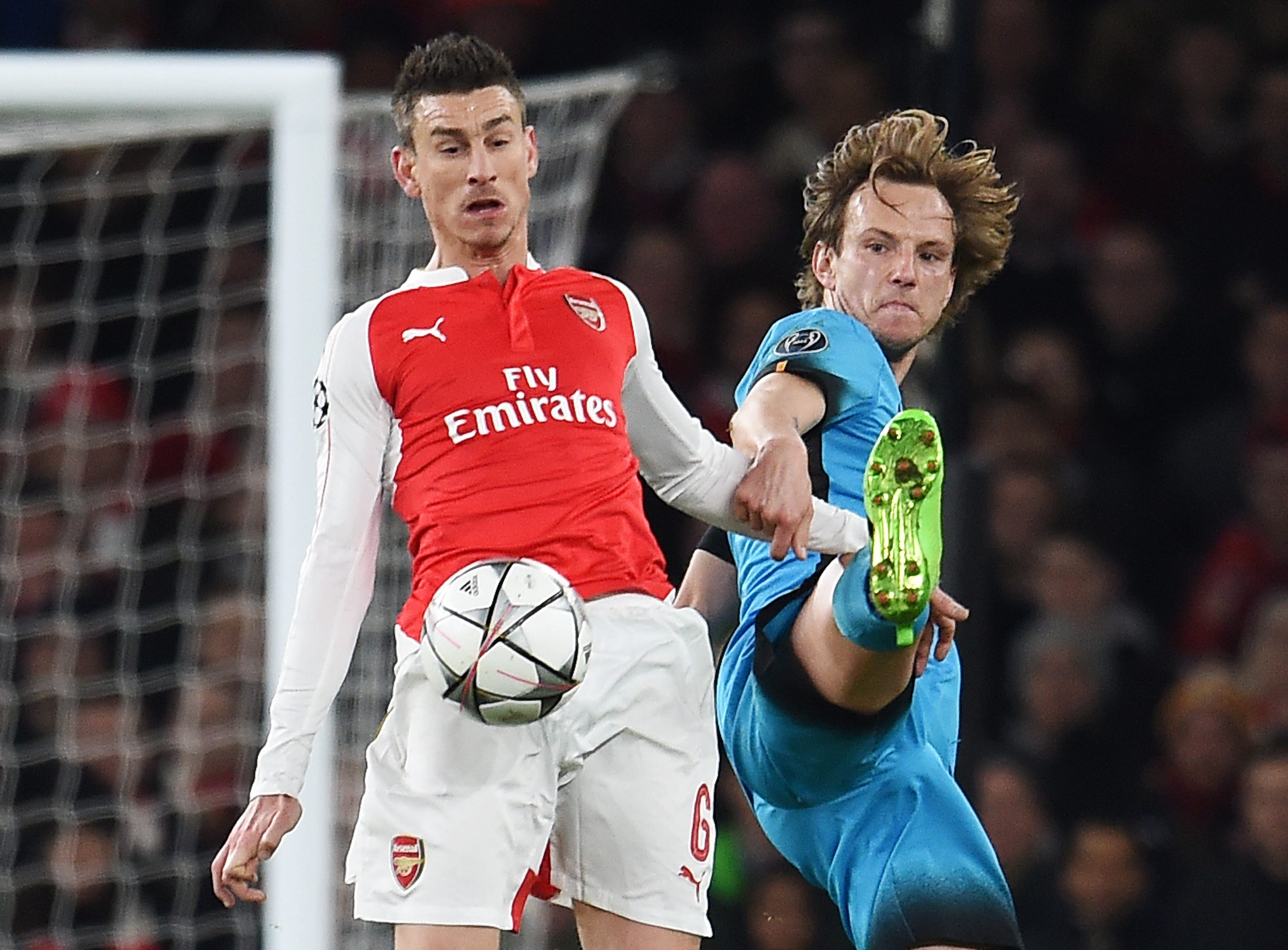 Arsenal's Laurent Koscielny (L) vies for the ball with Barcelona's Ivan Rakitic (R) during the UEFA Champions League Round of 16 first leg soccer match between Arsenal and Barcelona at the Emirates Stadium in London, Britain, 23 February 2016. EPA/ANDY RAIN