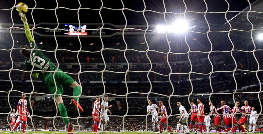 epa03493602 Atletico Madrid's Belgian goalkeeper Thibaut Courtois (L) tries to stop a shot from Portuguese forward Cristiano Ronaldo of Real Madrid during their Spanish Liga's Primera Division match at Santiago Bernabeu stadium in Madrid, central Spain, 01 December 2012. EPA/JUANJO MARTIN