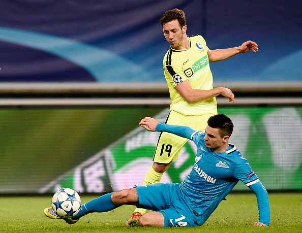Gent's Belgian midfielder Brecht Dejaegere (top) vies for the ball against Zenit's defender Artur Yusupov during the UEFA Champions' League, Group H, football match KAA Gent vs FC Zenit on December 9, 2015 at the KAA Gent Stadium in Gent. Gent won 2-1. AFP PHOTO / JOHN THYS / AFP / JOHN THYS (Photo credit should read JOHN THYS/AFP/Getty Images)