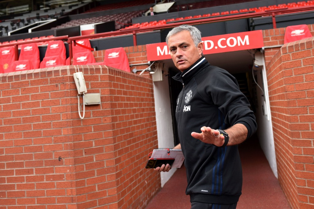 Manchester United's new Portuguese manager Jose Mourinho arrives to pose with a football shirt during a photocall on the pitch at Old Trafford stadium in Manchester, northern England, on July 5, 2016. Jose Mourinho officially started work as Manchester United manager at the club's Carrington training base yesterday. The 53-year-old was appointed as United boss in May after the sacking of Dutchman Louis van Gaal. (Photo credit: Oli Scarff/AFP/Getty Images)