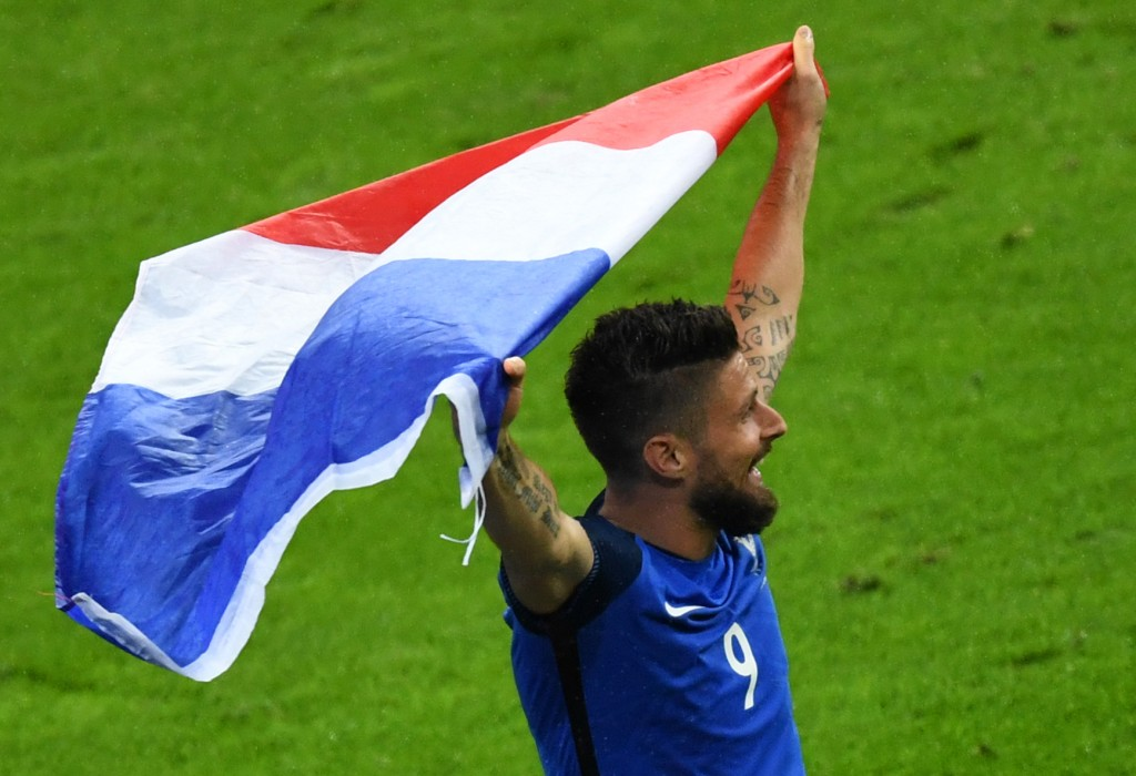 France's forward Olivier Giroud holds a French flag after winning the Euro 2016 quarter-final football match between France and Iceland at the Stade de France in Saint-Denis, near Paris, on July 3, 2016. / AFP / Francisco LEONG (Photo credit should read FRANCISCO LEONG/AFP/Getty Images)