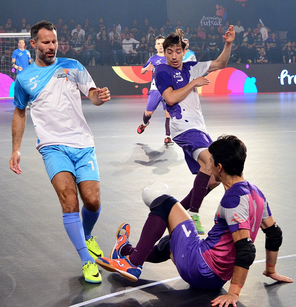 Former Manchester United footballer Ryan Giggs (L) is tackled while taking part in the final of the Indian Premier Futsal Football League match at The Peddem Indoor Stadium in Mapusa on July 24, 2016. / AFP / STR (Photo credit should read STR/AFP/Getty Images)