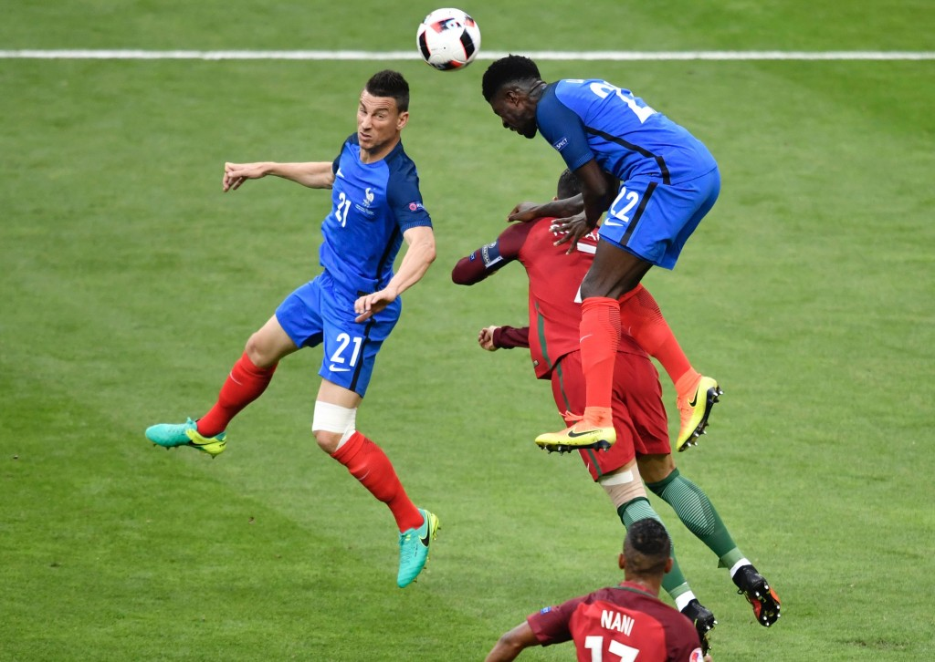 Portugal's forward Cristiano Ronaldo (hidden) vies for the ball with France's defender Laurent Koscielny (L) and France's defender Samuel Umtiti during the Euro 2016 final football match between Portugal and France at the Stade de France in Saint-Denis, north of Paris, on July 10, 2016. / AFP / PHILIPPE LOPEZ (Photo credit should read PHILIPPE LOPEZ/AFP/Getty Images)