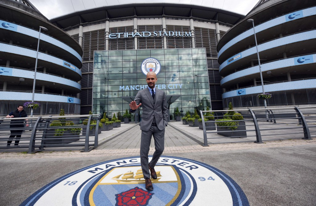 """Manchester City's Spanish football coach Pep Guardiola poses for photographs outside the Etihad Stadium in Manchester, northern England, on July 8, 2016. Pep Guardiola has warned his Manchester City players that they have to prove themselves all over again following his arrival at the club. / AFP / OLI SCARFF / RESTRICTED TO EDITORIAL USE. NO USE WITH UNAUTHORIZED AUDIO, VIDEO, DATA, FIXTURE LISTS, CLUB/LEAGUE LOGOS OR """"LIVE"""" SERVICES. ONLINE IN-MATCH USE LIMITED TO 45 IMAGES, NO VIDEO EMULATION. NO USE IN BETTING, GAMES OR SINGLE CLUB/LEAGUE/PLAYER PUBLICATIONS. (Photo credit should read OLI SCARFF/AFP/Getty Images)"""