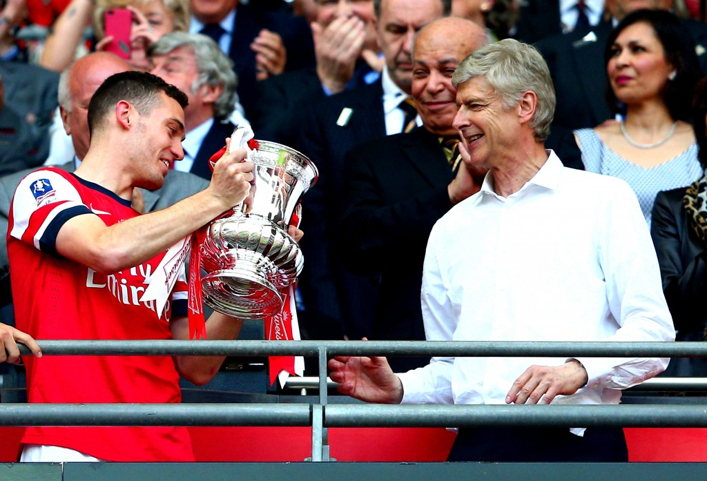 LONDON, ENGLAND - MAY 17: Captain Thomas Vermaelen of Arsenal passes the trophy to Arsene Wenger manager of Arsenal (R) after the FA Cup with Budweiser Final match between Arsenal and Hull City at Wembley Stadium on May 17, 2014 in London, England. (Photo by Clive Mason/Getty Images)