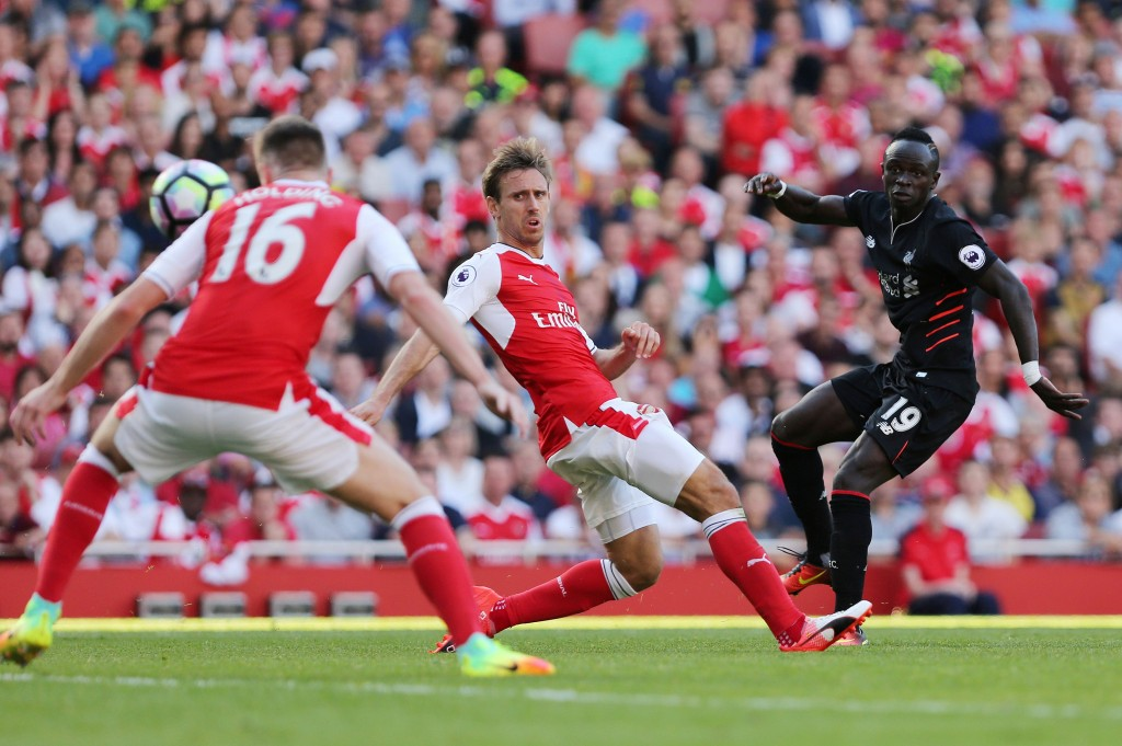 Liverpool's Senegalese midfielder Sadio Mane (R) scores Liverpool's fourth goal during the English Premier League football match between Arsenal and Liverpool at the Emirates Stadium in London on August 14, 2016. / AFP / Lee MILLS / RESTRICTED TO EDITORIAL USE. No use with unauthorized audio, video, data, fixture lists, club/league logos or 'live' services. Online in-match use limited to 75 images, no video emulation. No use in betting, games or single club/league/player publications. / (Photo credit should read LEE MILLS/AFP/Getty Images)