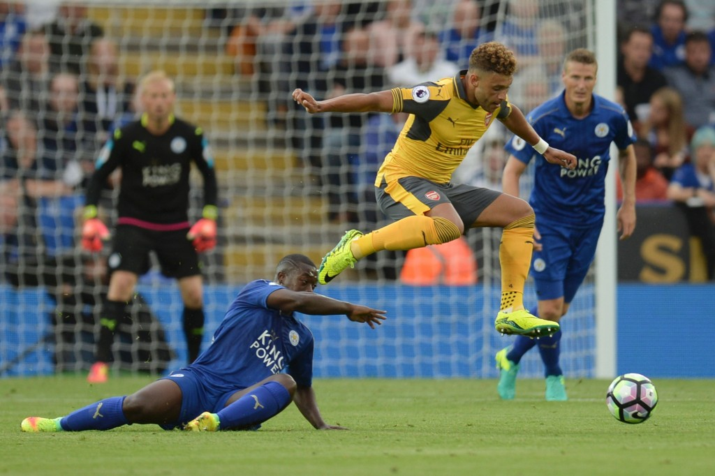Arsenal's English midfielder Alex Oxlade-Chamberlain (C) jumps a challenge from Leicester City's French midfielder Nampalys Mendy (L) during the English Premier League football match between Leicester City and Arsenal at King Power Stadium in Leicester, central England on August 20, 2016. (Photo credit: Oli Scarff/AFP/Getty Images)