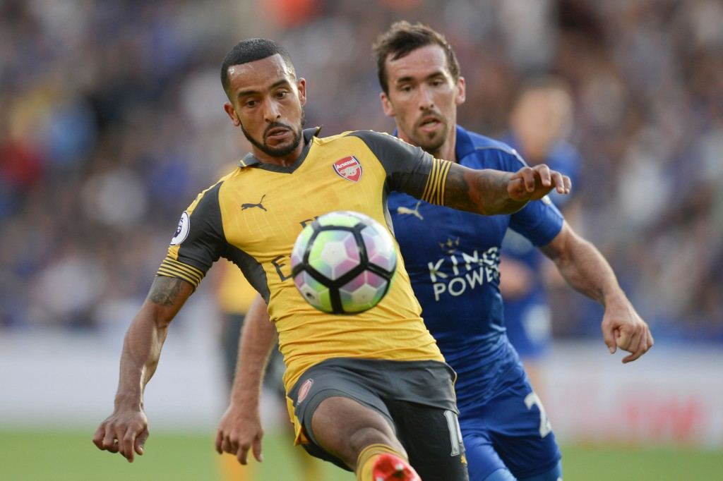 Arsenal's English midfielder Theo Walcott (L) tries to hold off Leicester City's Austrian defender Christian Fuchs (R) during the English Premier League football match between Leicester City and Arsenal at King Power Stadium in Leicester, central England on August 20, 2016. (Photo credit: Oli Scarff/AFP/Getty Images)