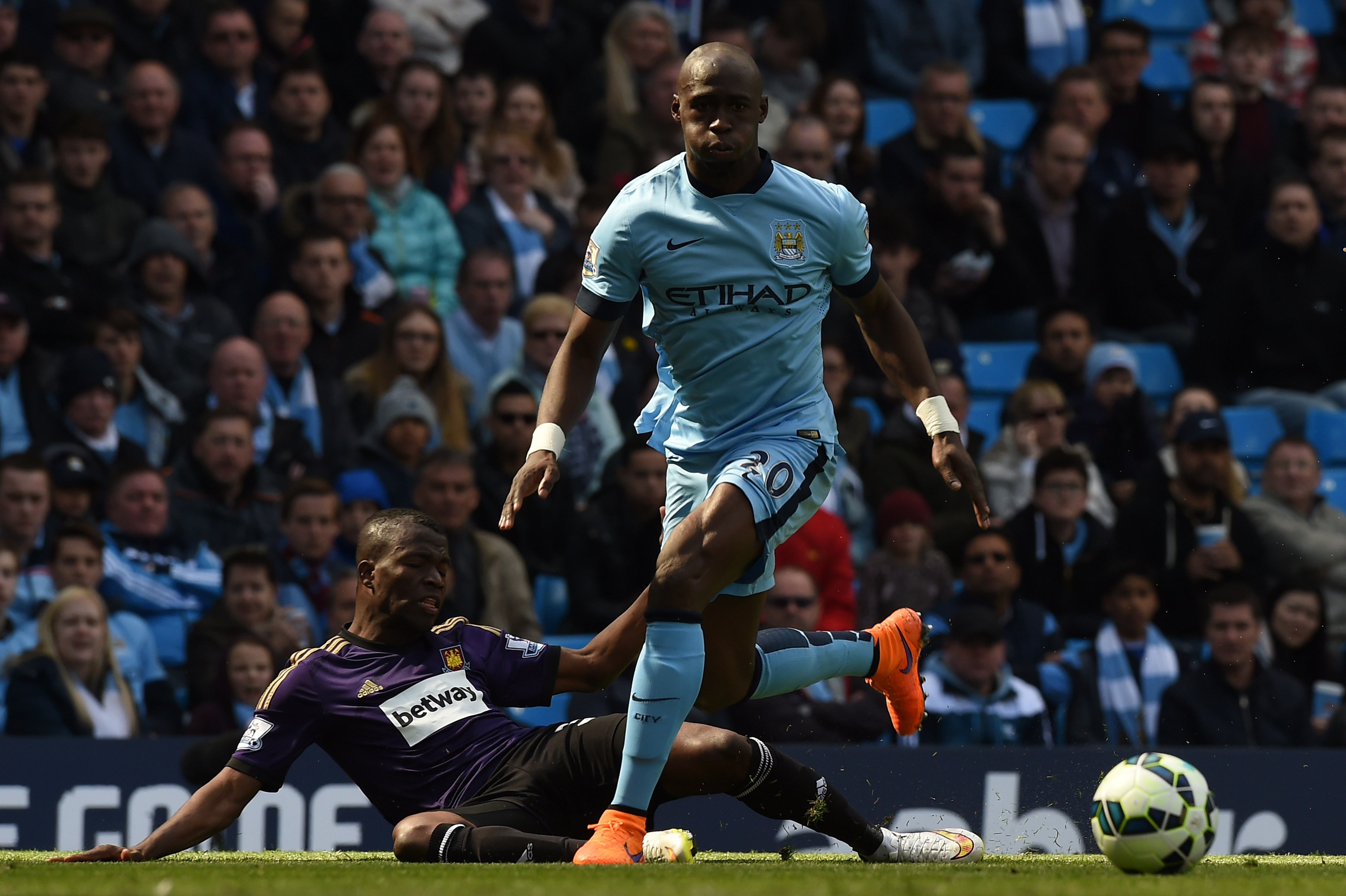 Manchester City's French defender Eliaquim Mangala (R) beats West Ham United's Cameroonian midfielder Alex Song (L) during the English Premier League football match between Manchester City and West Ham United at the Etihad Stadium in Manchester, north west England on April 19, 2015. AFP PHOTO / PAUL ELLIS RESTRICTED TO EDITORIAL USE. No use with unauthorized audio, video, data, fixture lists, club/league logos or live services. Online in-match use limited to 45 images, no video emulation. No use in betting, games or single club/league/player publications. (Photo credit should read PAUL ELLIS/AFP/Getty Images)