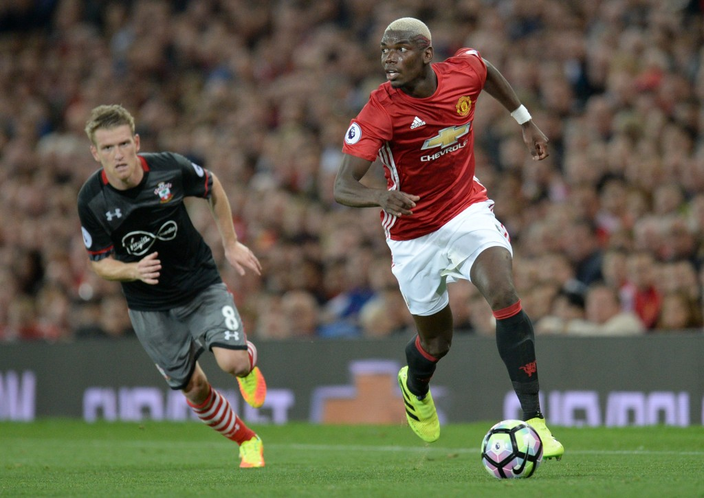 Manchester United's French midfielder Paul Pogba (R) runs with the ball during the English Premier League football match between Manchester United and Southampton at Old Trafford in Manchester, north west England, on August 19, 2016. / AFP / Oli SCARFF / RESTRICTED TO EDITORIAL USE. No use with unauthorized audio, video, data, fixture lists, club/league logos or 'live' services. Online in-match use limited to 75 images, no video emulation. No use in betting, games or single club/league/player publications. / (Photo credit should read OLI SCARFF/AFP/Getty Images)