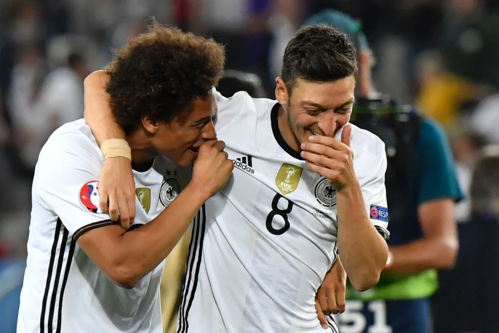 Germany's midfielder Mesut Oezil (R) and Germany's midfielder Leroy Sane celebrate after winning the Euro 2016 quarter-final football match between Germany and Italy at the Matmut Atlantique stadium in Bordeaux on July 2, 2016. (Photo credit: Georges Gobet/AFP/Getty Images)