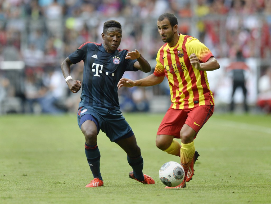 """Bayern Munich's Austrian midfielder David Alaba (L) and Barcelona's defender Martin Montoya vie for the ball during the """"Uli Hoeness Cup"""" friendly football match FC Bayern Munich vs FC Barcelona in the stadium in Munich, southern Germany, on July 24, 2013. AFP PHOTO/CHRISTOF STACHE (Photo credit should read CHRISTOF STACHE/AFP/Getty Images)"""