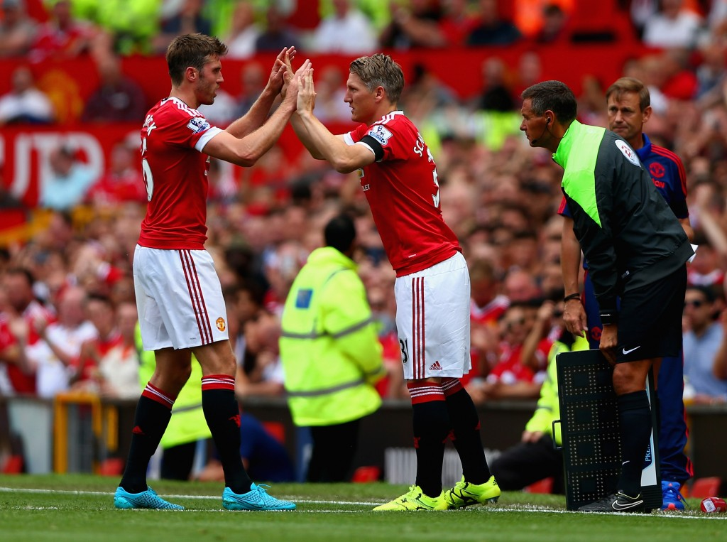MANCHESTER, ENGLAND - AUGUST 08: Bastian Schweinsteiger of Manchester United high fives with his team mate Michael Carrick during the Barclays Premier League match between Manchester United and Tottenham Hotspur at Old Trafford on August 8, 2015 in Manchester, England. (Photo by Clive Brunskill/Getty Images)