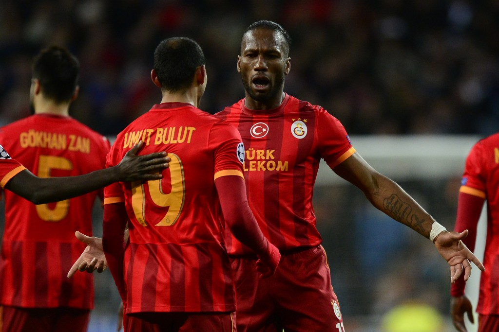 Galatasaray's striker Umut Bulut (L) celebrates with Galatasaray's Ivorian forward Didier Drogba after scoring their team first goal during the UEFA Champions League football match Real Madrid CF vs Galatasaray SK at the Santiago Bernabeu stadium in Madrid on November 27, 2013. AFP PHOTO/ JAVIER SORIANO (Photo credit should read JAVIER SORIANO/AFP/Getty Images)