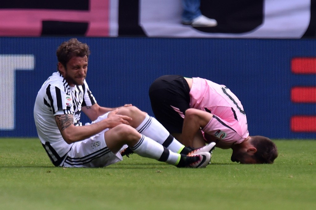 TURIN, ITALY - APRIL 17: Claudio Marchisio (L) of Juventus and Franco Vazquez of Palermo lie on the pitch after an injury during the Serie A match between Juventus FC and US Citta di Palermo at Juventus Arena on April 17, 2016 in Turin, Italy. (Photo by Tullio M. Puglia/Getty Images)