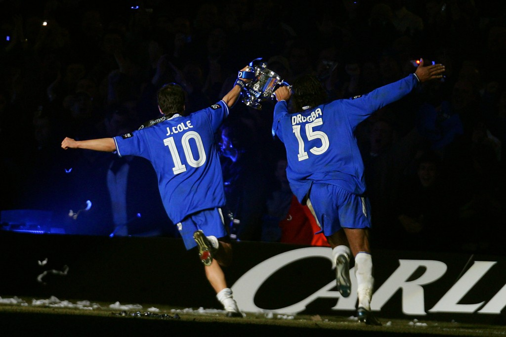 Chelsea's Joe Cole (L) and Didier Drogba run with the Carling Cup trophy after defeating Liverpool in the Carling Cup Final football match at the Millennium Dome in Cardiff, Wales, 27 February, 2005. Chelsea won 3-2 in extra time. AFP PHOTO/JIM WATSON NO TELCOS, WEBSITES SUBJECT TO SUBCRIPTION OF LICENCE WITH FAPL AT WWW.FAPLWEB.COM (Photo credit should read JIM WATSON/AFP/Getty Images)