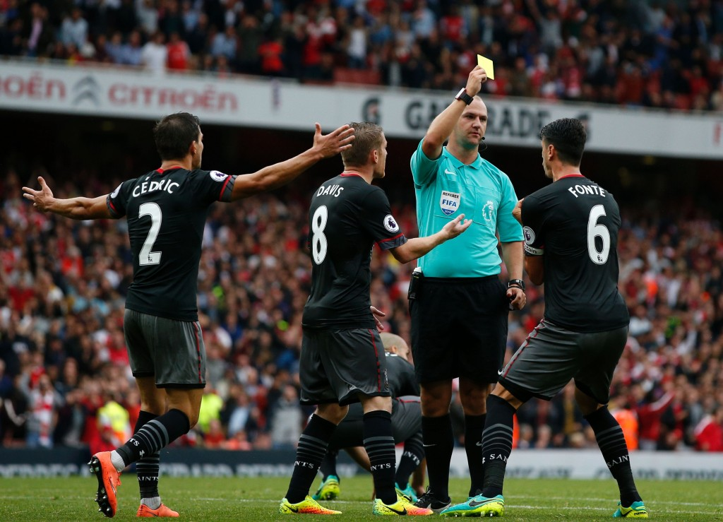 Referee Robert Madley shows a yellow card to Southampton's Portuguese defender Jose Fonte as he gives away a late penalty during the English Premier League football match between Arsenal and Southampton at the Emirates Stadium in London on September 10, 2016. Arsenal won the game 2-1. / AFP / Adrian DENNIS / RESTRICTED TO EDITORIAL USE. No use with unauthorized audio, video, data, fixture lists, club/league logos or 'live' services. Online in-match use limited to 75 images, no video emulation. No use in betting, games or single club/league/player publications. / (Photo credit should read ADRIAN DENNIS/AFP/Getty Images)