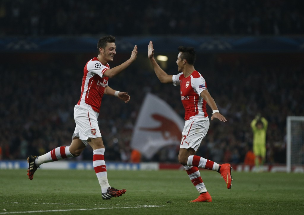 Arsenal's Chilean striker Alexis Sanchez (R) celebrates scoring his goal with Arsenal's German midfielder Mesut Ozil (L) during the UEFA Champions League, Group D football match between Arsenal and Galatasaray at The Emirates Stadium in north London on October 1, 2014. Arsenal won the game 4-1. (Photo by Adrian Dennis/AFP/Getty Images)