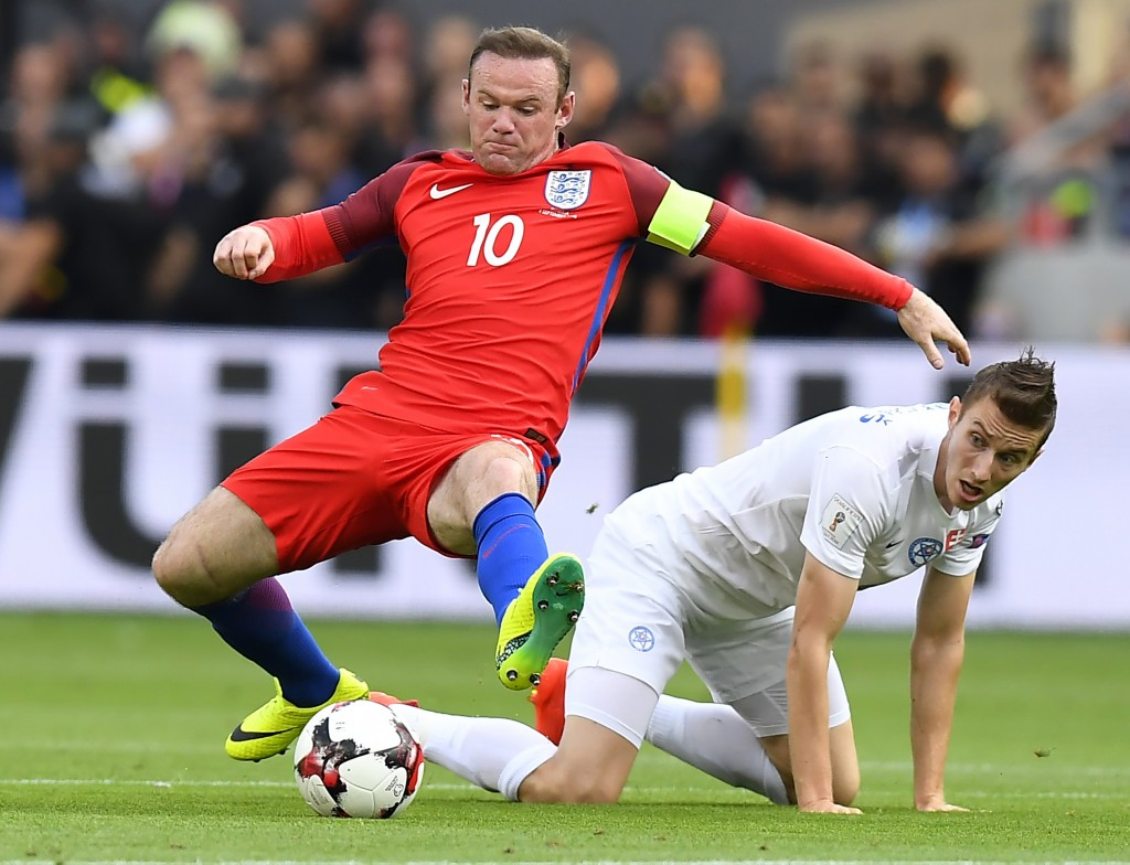 England's forward Wayne Rooney (L) vies with Slovakia's midfielder Jan Gregus during the World Cup 2018 football qualification match between Slovakia and England in Trnava, Slovakia, on September 4, 2015. (Photo by Joe Klamar/AFP/Getty Images)