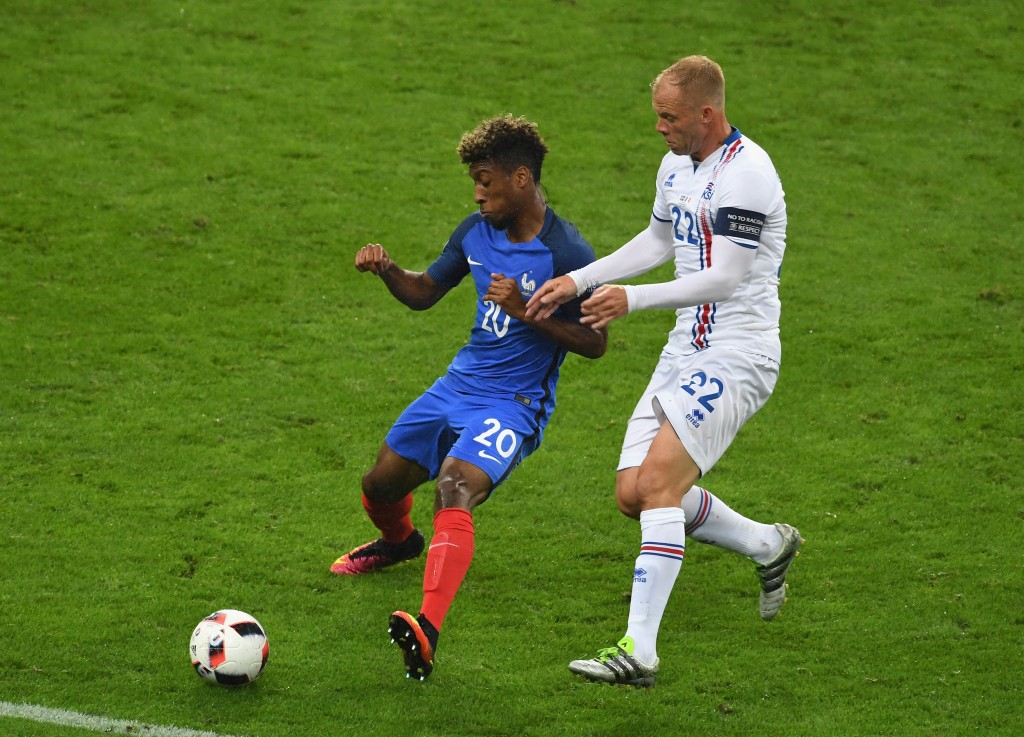 PARIS, FRANCE - JULY 03: Kingsley Coman of France and Eidur Gudjohnsen of Iceland compete for the ball during the UEFA EURO 2016 quarter final match between France and Iceland at Stade de France on July 3, 2016 in Paris, France. (Photo by Michael Regan/Getty Images)