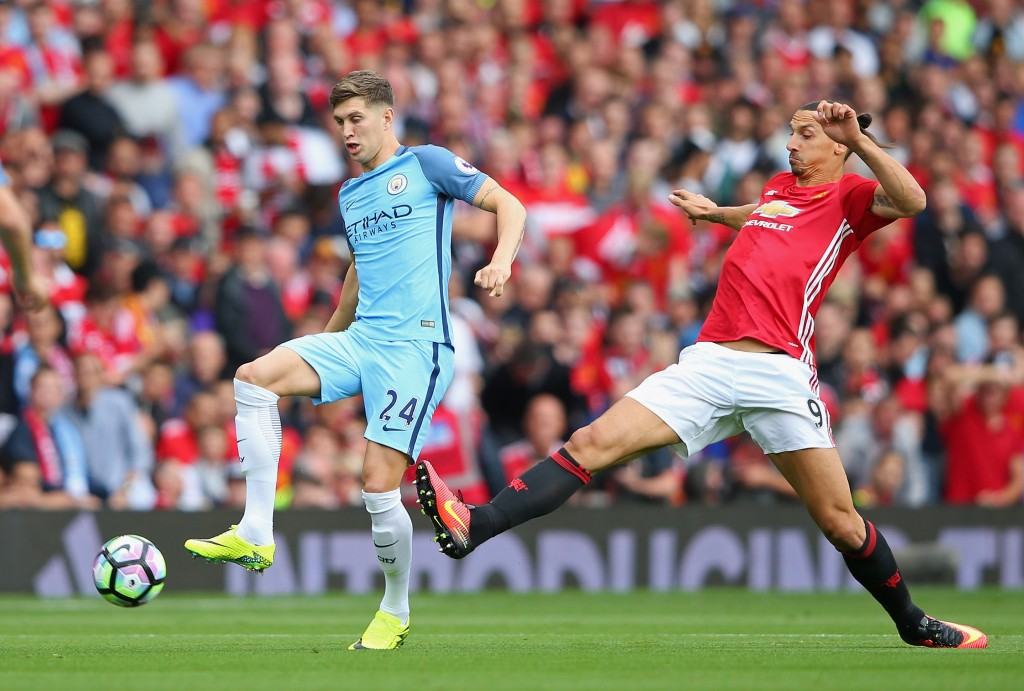 MANCHESTER, ENGLAND - SEPTEMBER 10: Zlatan Ibrahimovic of Manchester United is tackled by John Stones of Manchester City during the Premier League match between Manchester United and Manchester City at Old Trafford on September 10, 2016 in Manchester, England. (Photo by Alex Livesey/Getty Images)