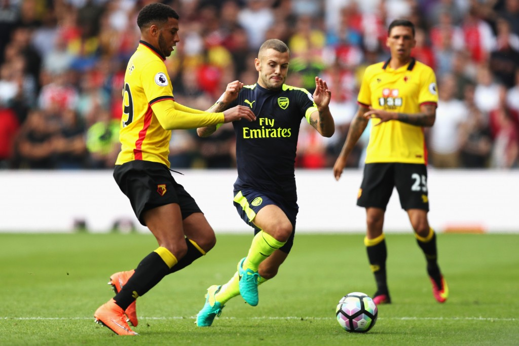 WATFORD, ENGLAND - AUGUST 27: Etienne Capoue of Watford (L) and Jack Wilshere of Arsenal (C) both challenge for the ball during the Premier League match between Watford and Arsenal at Vicarage Road on August 27, 2016 in Watford, England. (Photo by Christopher Lee/Getty Images)