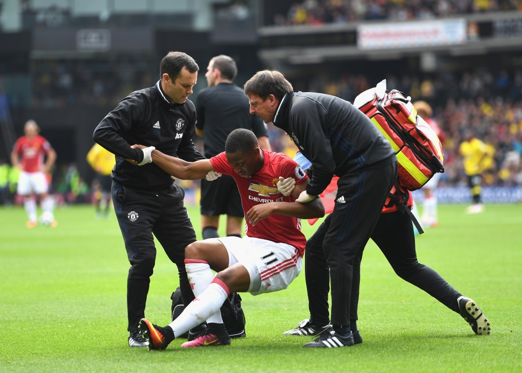 WATFORD, ENGLAND - SEPTEMBER 18: The Manchester United medical staff help Anthony Martial of Manchester United up after being injured during the Premier League match between Watford and Manchester United at Vicarage Road on September 18, 2016 in Watford, England. (Photo by Laurence Griffiths/Getty Images)