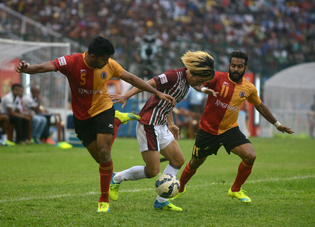 Katsumi Yusa(C)of Mohun Bagan is tackled by East Bengal's Rahul Bheke (L) and Cavin Peter Lobo(R)during the I-League football match at The Kanchenjungha Stadium in Siliguri on April 2, 2016. East Bengal won the match 2-1. / AFP / DIPTENDU DUTTA        (Photo credit should read DIPTENDU DUTTA/AFP/Getty Images)