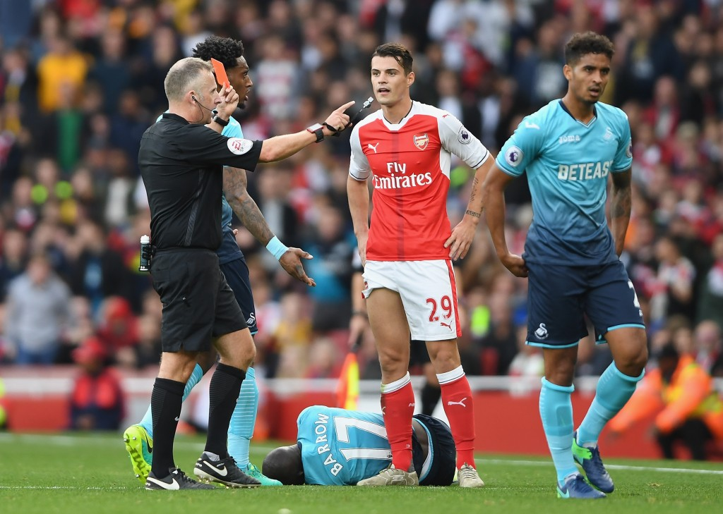 LONDON, ENGLAND - OCTOBER 15: Referee Jonanthan Moss (L) shows Granit Xhaka of Arsenal (C) a red card for a foul on Modou Barrow of Swansea City during the Premier League match between Arsenal and Swansea City at Emirates Stadium on October 15, 2016 in London, England. (Photo by Mike Hewitt/Getty Images)