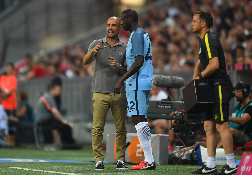 MUNICH, GERMANY - JULY 20: Pep Guardiola the manager of Manchester City speaks with substitute Yaya Toure of Manchester City during the pre season friendly match between Bayern Muenchen and Manchester City F.C at the Allianz Arena on July 20, 2016 in Munich, Germany. (Photo by Lennart Preiss/Bongarts/Getty Images)
