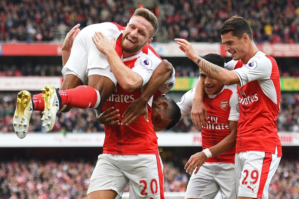 Arsenal's English midfielder Theo Walcott (L) celebrates with Arsenal's German defender Shkodran Mustafi (2nd L) Arsenal's Chilean striker Alexis Sanchez (2nd R) and Arsenal's Swiss midfielder Granit Xhaka (R) after scoring their second goal during the English Premier League football match between Arsenal and Swansea City at the Emirates Stadium in London on October 15, 2016.  Arsenal won the game 3-2. / AFP / Justin TALLIS / RESTRICTED TO EDITORIAL USE. No use with unauthorized audio, video, data, fixture lists, club/league logos or 'live' services. Online in-match use limited to 75 images, no video emulation. No use in betting, games or single club/league/player publications.  /         (Photo credit should read JUSTIN TALLIS/AFP/Getty Images)