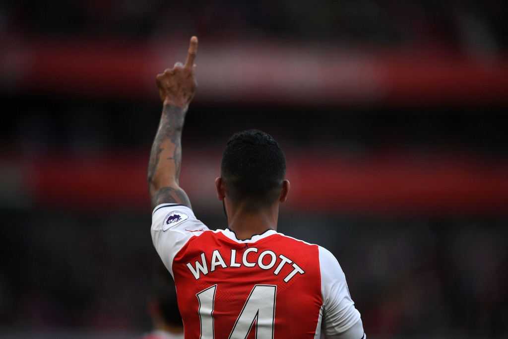 Arsenal's English midfielder Theo Walcott celebrates scoring the opening goal of the English Premier League football match between Arsenal and Swansea City at the Emirates Stadium in London on October 15, 2016. Arsenal won the game 3-2. / AFP / Justin TALLIS / RESTRICTED TO EDITORIAL USE. No use with unauthorized audio, video, data, fixture lists, club/league logos or 'live' services. Online in-match use limited to 75 images, no video emulation. No use in betting, games or single club/league/player publications. / (Photo credit should read JUSTIN TALLIS/AFP/Getty Images)
