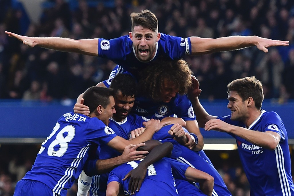 Chelsea's English defender Gary Cahill (top) jumps onto the huddle to join the celebrates after Chelsea's French midfielder N'Golo Kante scored their fourth goal during the English Premier League football match between Chelsea and Manchester United at Stamford Bridge in London on October 23, 2016. / AFP / GLYN KIRK / RESTRICTED TO EDITORIAL USE. No use with unauthorized audio, video, data, fixture lists, club/league logos or 'live' services. Online in-match use limited to 75 images, no video emulation. No use in betting, games or single club/league/player publications. / (Photo credit should read GLYN KIRK/AFP/Getty Images)