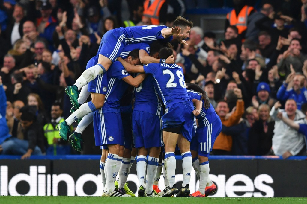 Chelsea's English defender Gary Cahill (top) jumps onto the huddle to join the celebrates after Chelsea's French midfielder N'Golo Kante scored their fourth goal during the English Premier League football match between Chelsea and Manchester United at Stamford Bridge in London on October 23, 2016. / AFP / BEN STANSALL / RESTRICTED TO EDITORIAL USE. No use with unauthorized audio, video, data, fixture lists, club/league logos or 'live' services. Online in-match use limited to 75 images, no video emulation. No use in betting, games or single club/league/player publications. / (Photo credit should read BEN STANSALL/AFP/Getty Images)