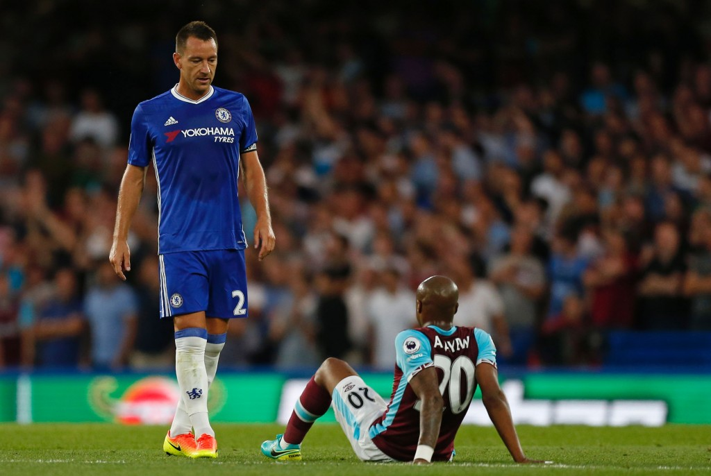 Chelsea's English defender John Terry (L) walks past an injured West Ham United's French-born Ghanaian midfielder Andre Ayew during the English Premier League football match between Chelsea and West Ham United at Stamford Bridge in London on August 15, 2016. / AFP / Ian KINGTON / RESTRICTED TO EDITORIAL USE. No use with unauthorized audio, video, data, fixture lists, club/league logos or 'live' services. Online in-match use limited to 75 images, no video emulation. No use in betting, games or single club/league/player publications. / (Photo credit should read IAN KINGTON/AFP/Getty Images)