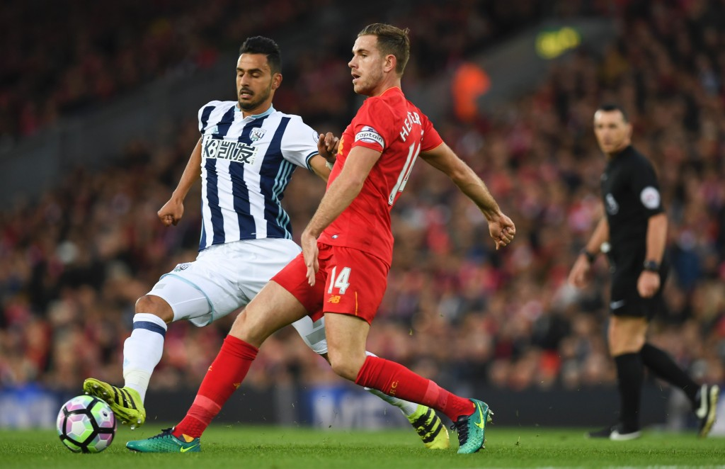 Liverpool's English midfielder Jordan Henderson (R) plays the ball in front of West Bromwich Albion's Belgian midfielder Nacer Chadli (L) during the English Premier League football match between Liverpool and West Bromwich Albion at Anfield in Liverpool, north west England on October 22, 2016. / AFP / PAUL ELLIS / RESTRICTED TO EDITORIAL USE. No use with unauthorized audio, video, data, fixture lists, club/league logos or 'live' services. Online in-match use limited to 75 images, no video emulation. No use in betting, games or single club/league/player publications. / (Photo credit should read PAUL ELLIS/AFP/Getty Images)