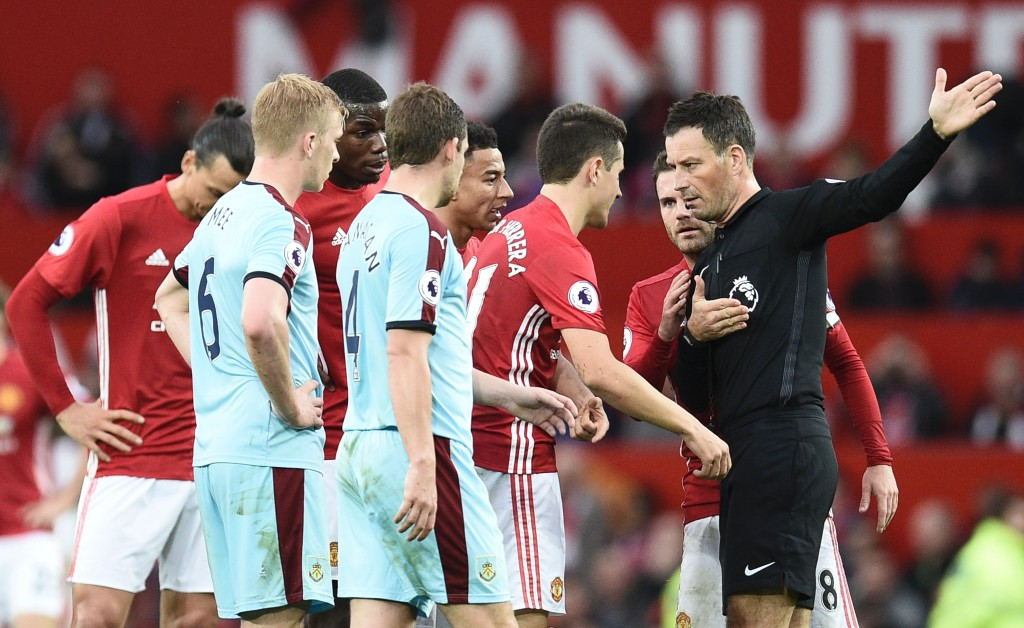 Referee Mark Clattenburg (R) gestures to Manchester United's Spanish midfielder Ander Herrera (2R) to leave the field after being sent off during the English Premier League football match between Manchester United and Burnley at Old Trafford in Manchester, north west England, on October 29, 2016. (Photo by Oli Scarff/AFP/Getty Images)