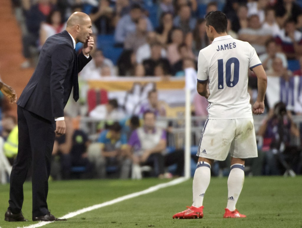 Real Madrid's French coach Zinedine Zidane (L) talks with Real Madrid's Colombian midfielder James Rodriguez during the Spanish league football match Real Madrid CF vs Villarreal CF at the Santiago Bernabeu stadium in Madrid on September 21, 2016. / AFP / CURTO DE LA TORRE (Photo credit should read CURTO DE LA TORRE/AFP/Getty Images)