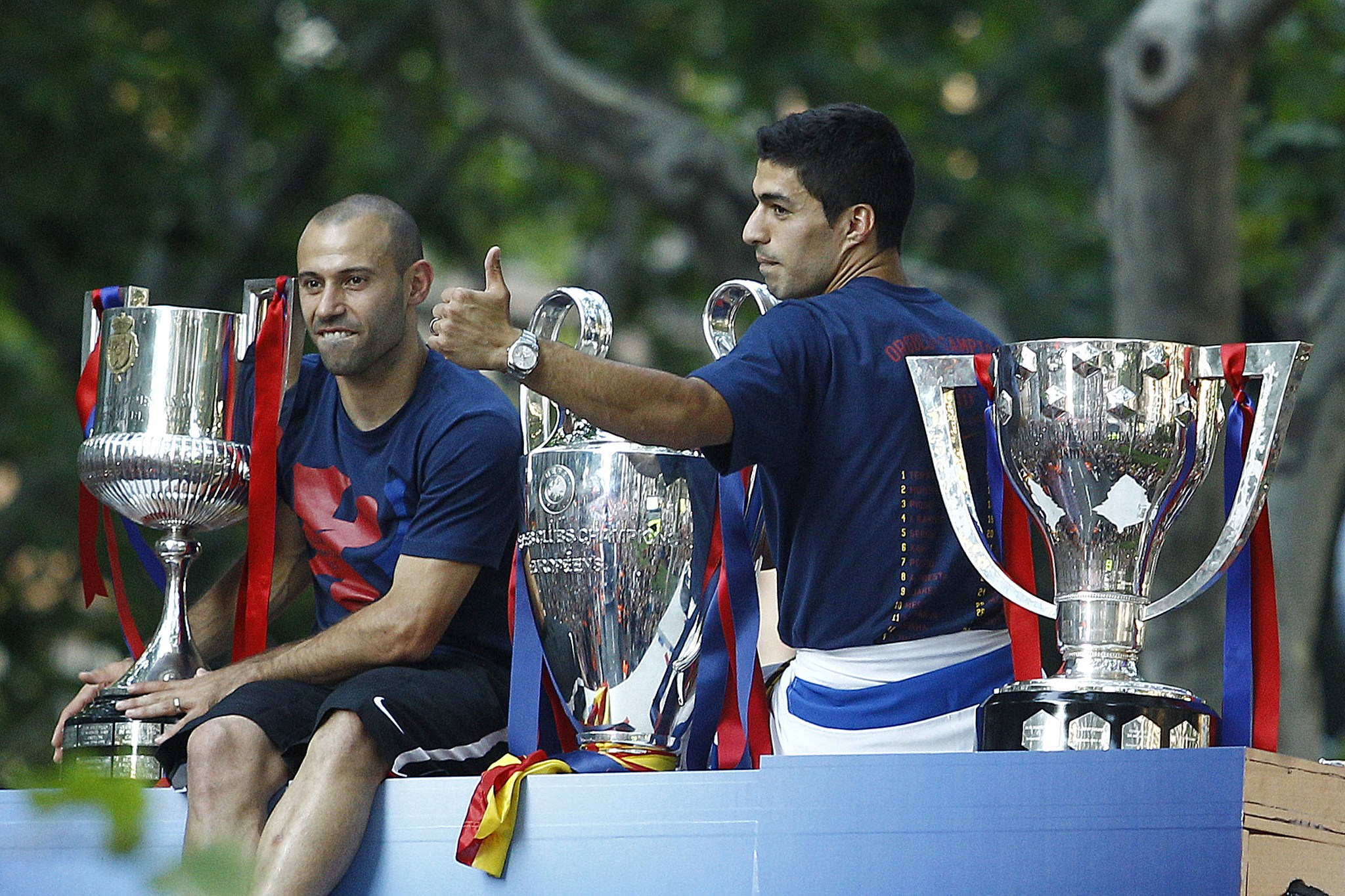 Barcelona's Uruguayan forward Luis Suarez (R) and Barcelona's Argentinian defender Javier Mascherano pose with the three trophies on a bus parading through the streets of Barcelona as the team celebrate its victory over Juventus one day after the UEFA Champions League final football on June 7, 2015. Luis Suarez and Neymar scored second-half goals to give Barcelona a 3-1 Champions League final victory over Juventus on June 6, 2015 as the Spaniards became the first team to twice win the European treble. AFP PHOTO/ QUIQUE GARCIA (Photo credit should read QUIQUE GARCIA/AFP/Getty Images)