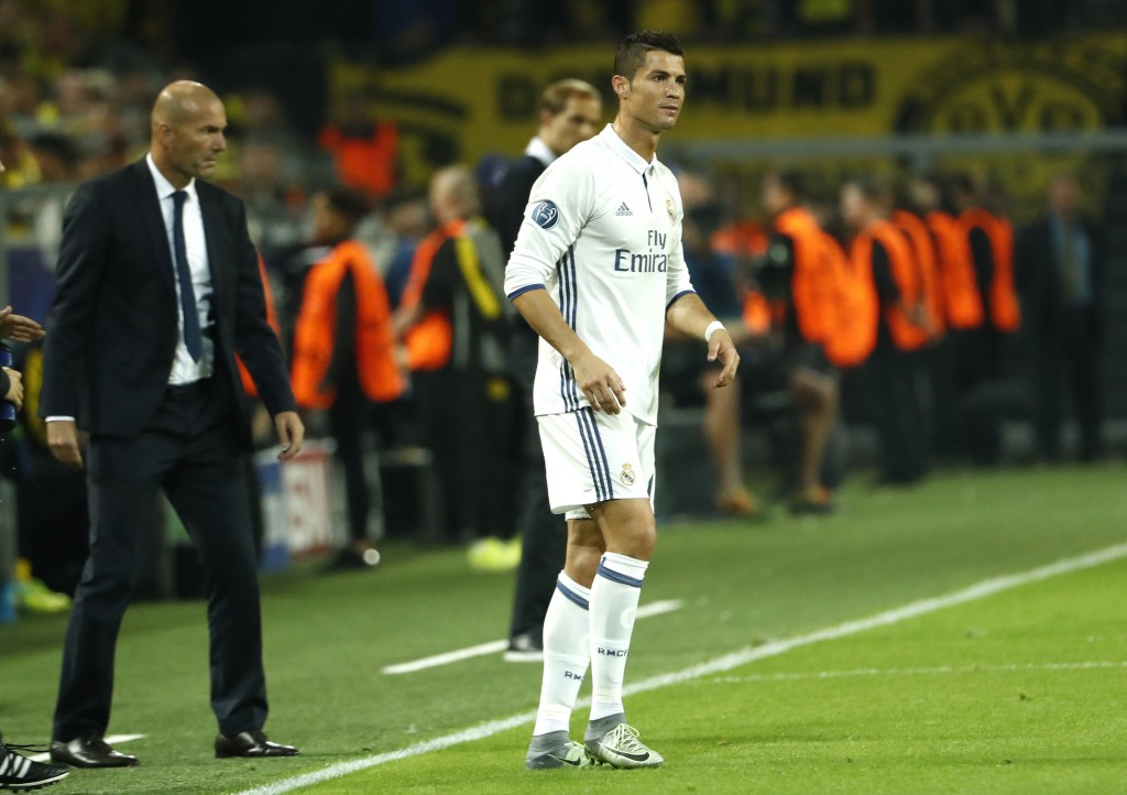 Real Madrid's French coach Zinedine Zidane (L) and Real Madrid's Portuguese forward Cristiano Ronaldo react during the UEFA Champions League first leg football match between Borussia Dortmund and Real Madrid at BVB stadium in Dortmund, on September 27, 2016. / AFP / Odd ANDERSEN (Photo credit should read ODD ANDERSEN/AFP/Getty Images)