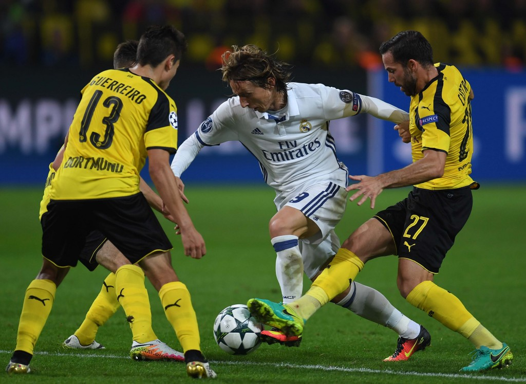 Dortmund's midfielder Gonzalo Castro (R) and Dortmund's Portuguese defender Raphael Guerreiro vie with Real Madrid's Croatian midfielder Luka Modric during the UEFA Champions League first leg football match between Borussia Dortmund and Real Madrid at BVB stadium in Dortmund, on September 27, 2016. / AFP / PATRIK STOLLARZ (Photo credit should read PATRIK STOLLARZ/AFP/Getty Images)