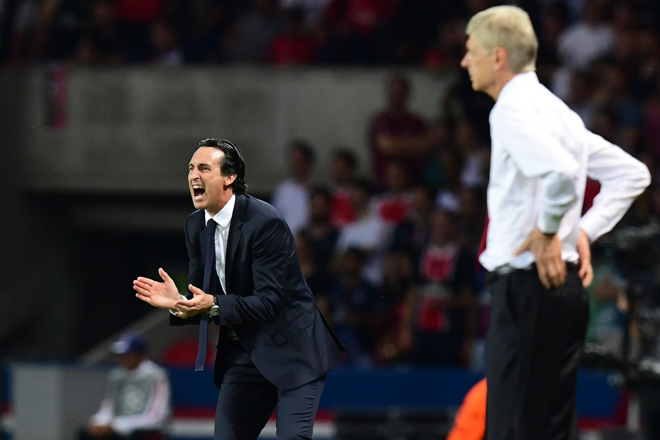 Paris Saint-Germain's Spanish head coach Unai Emery (L) gestures next to Arsenal's French manager Arsene Wenger during the UEFA Champions League Group A football match between Paris-Saint-Germain vs Arsenal FC, on September 13, 2016 at the Parc des Princes stadium in Paris. AFP PHOTO / FRANCK FIFE / AFP / FRANCK FIFE (Photo credit should read FRANCK FIFE/AFP/Getty Images)