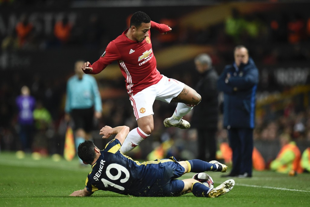 Fenerbahce's Turkish defender Sener Ozbayrakli (floor) slides to tackle Manchester United's Dutch midfielder Memphis Depay (top) during the UEFA Europa League group A football match between Manchester United and Fenerbahce at Old Trafford in Manchester, north west England, on October 20, 2016. / AFP / OLI SCARFF (Photo credit should read OLI SCARFF/AFP/Getty Images)