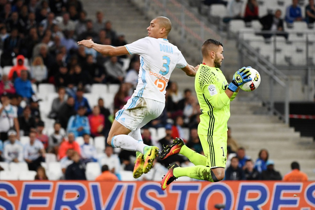Olympique de Marseille's Brazilian defender Matheus 'Doria' Macedo (L) competes for the ball with Lyon's Portuguese goalkeeper Anthony Lopes during the French L1 football match Olympique of Marseille (OM) vs Lyon at the Velodrome stadium in Marseille on September 18, 2016. (Photo by Boris Horvat/AFP/Getty Images)