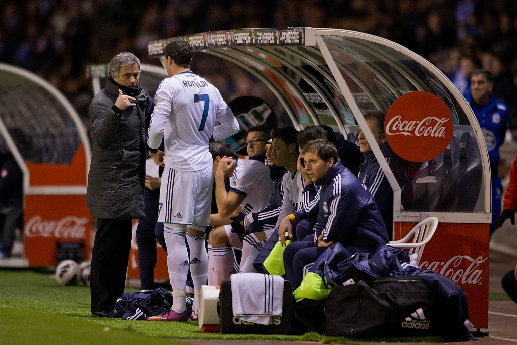 LA CORUNA, SPAIN - FEBRUARY 23: Head coach Jose Mourinho of Real Madrid CF gives instructions to Cristiano Ronaldo (2ndl) and Mezut Ozil (3dL) on the desk during the La Liga match between RC Deportivo La Coruna and Real Madrid CF at Riazor Stadium on February 23, 2013 in La Coruna, Spain. (Photo by Gonzalo Arroyo Moreno/Getty Images)