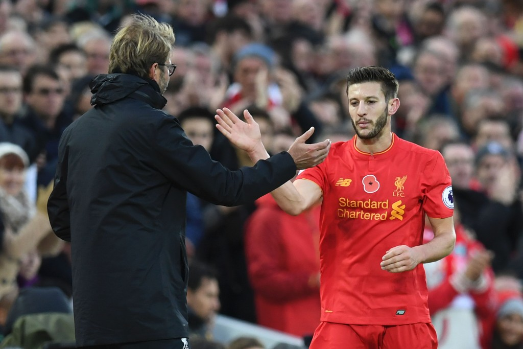 Liverpool's English midfielder Adam Lallana is congratulated by Liverpool's German manager Jurgen Klopp as he is substituted off of the pitch during the English Premier League football match between Liverpool and Watford at Anfield in Liverpool, north west England on November 6, 2016. / AFP / PAUL ELLIS / RESTRICTED TO EDITORIAL USE. No use with unauthorized audio, video, data, fixture lists, club/league logos or 'live' services. Online in-match use limited to 75 images, no video emulation. No use in betting, games or single club/league/player publications. / (Photo credit should read PAUL ELLIS/AFP/Getty Images)