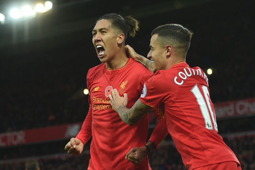 Liverpool's Brazilian midfielder Roberto Firmino (L) celebrates scoring his team's fourth goal with Liverpool's Brazilian midfielder Philippe Coutinho during the English Premier League football match between Liverpool and Watford at Anfield in Liverpool, north west England on November 6, 2016. / AFP / PAUL ELLIS / RESTRICTED TO EDITORIAL USE. No use with unauthorized audio, video, data, fixture lists, club/league logos or 'live' services. Online in-match use limited to 75 images, no video emulation. No use in betting, games or single club/league/player publications. / (Photo credit should read PAUL ELLIS/AFP/Getty Images)