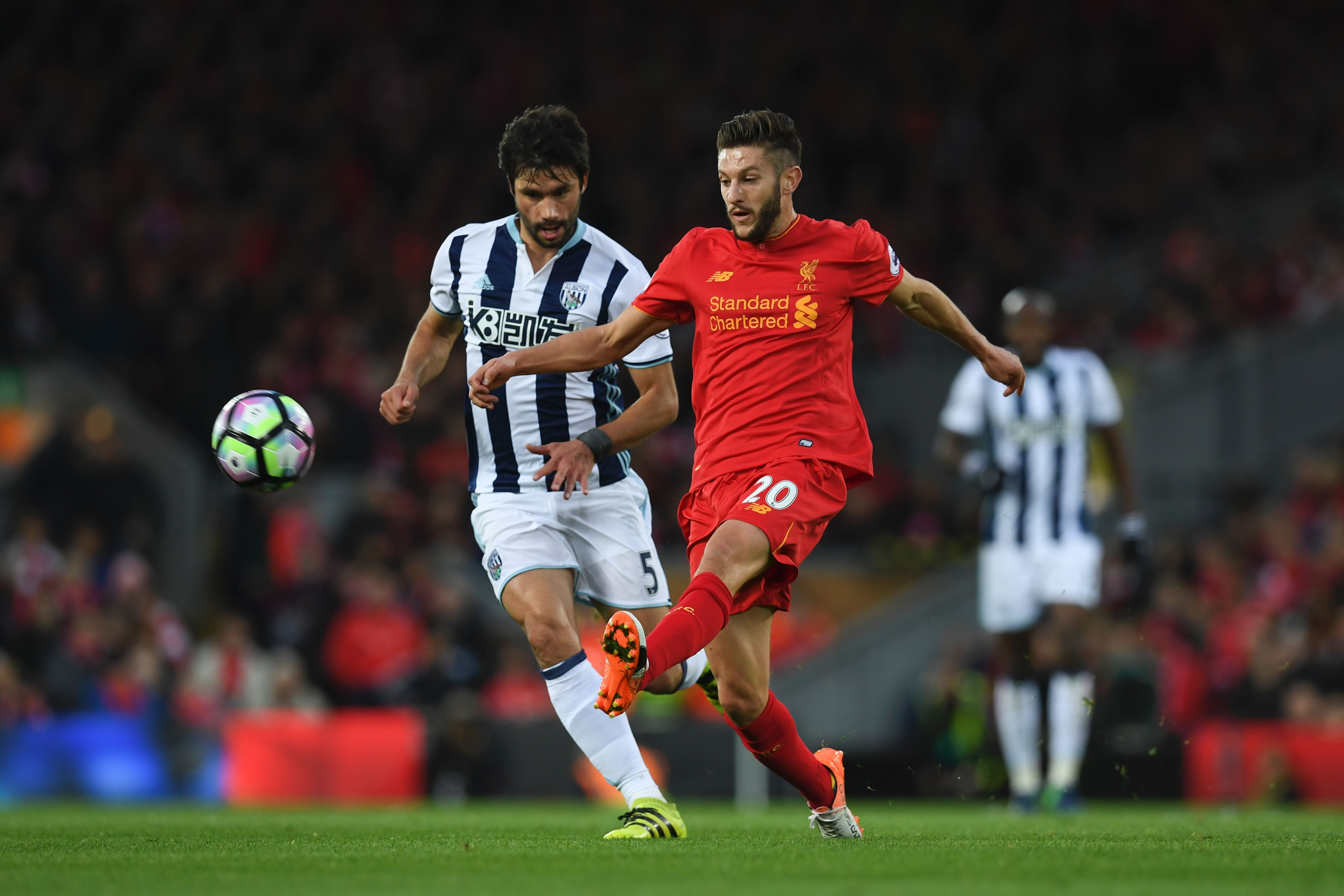 Liverpool's English midfielder Adam Lallana (R) plays the ball ahead of West Bromwich Albion's Argentinian midfielder Claudio Yacob (L) during the English Premier League football match between Liverpool and West Bromwich Albion at Anfield in Liverpool, north west England on October 22, 2016. / AFP / PAUL ELLIS / RESTRICTED TO EDITORIAL USE. No use with unauthorized audio, video, data, fixture lists, club/league logos or 'live' services. Online in-match use limited to 75 images, no video emulation. No use in betting, games or single club/league/player publications. / (Photo credit should read PAUL ELLIS/AFP/Getty Images)